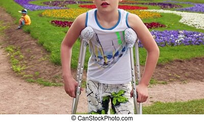 Boy stand with crutches, his injured leg has broken finger,...