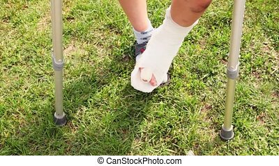 Boy makes steps by injured leg with broken finger, closeup...