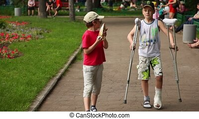 Boy walks with his friend on crutches and eats icecream in...
