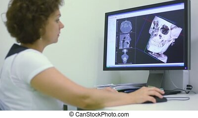 Doctor sits and watches x-ray picture of skull on display -...