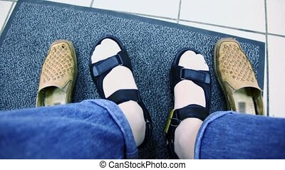 Mans feet in summer shoes and old pair stand near on carpet...