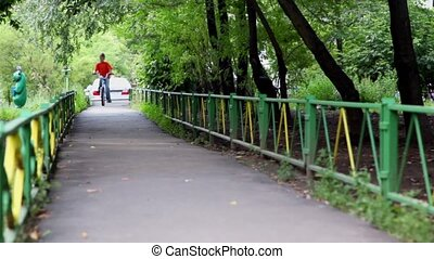 Little boy rides on bicycle by asphalt path under trees and...