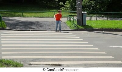 boy looks around and walks over road by pedestrian crossing...