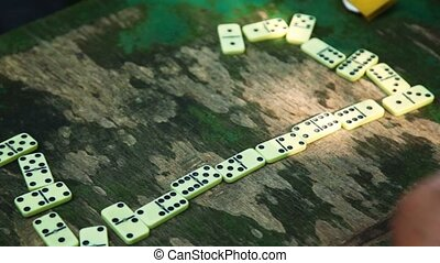 People play dominoes on table, only hands are visible -...