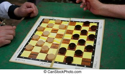 People play draughts on table, only hands are visible -...