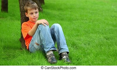 Little boy leans against tree on grass and looks around