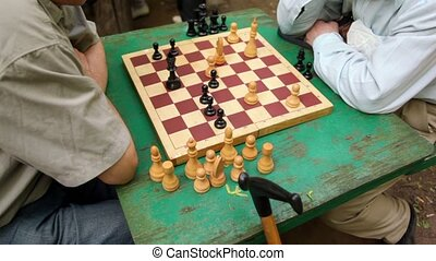 Two men sit and think under chessboard, closeup view of table