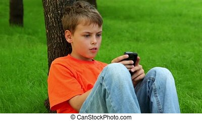 Little boy leans against tree on grass and plays with cell...