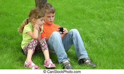 Two kids sit together at grass near tree - Two kids boy and...