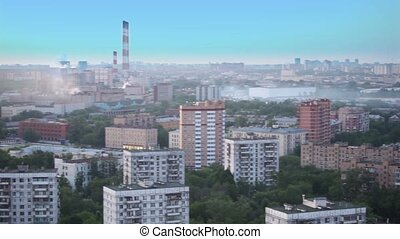 Panorama of city with houses among trees in fog at summer...