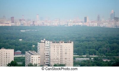 Panorama of Moscow with houses among trees at summer day