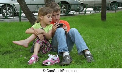 Two kids sit together, sister watches how brother plays -...