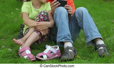 Two kids boy and girl sit together at grass near parking,...