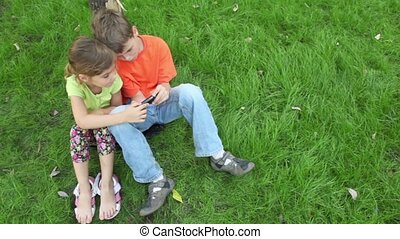 Two kids boy and girl sit together at grass near tree, sister watches how her brother plays with digital game on cell phone, view from above