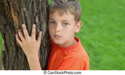 Little boy stands and embraces tree, closeup view at summer day