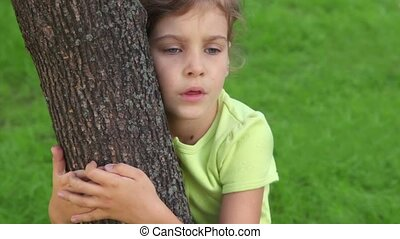 Little girl embraces tree and speaks, closeup view at summer day
