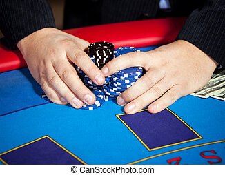 Hand with chips, and $ banknotes on table