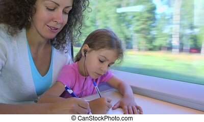 Little girl and mother draw by pens in book when sit at...