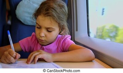 Little girl draws by pen on paper when sits at train near window