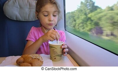 Little girl sits at table and mixes coffe near train window...