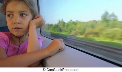 Little girl in headphones sits and watch at train window