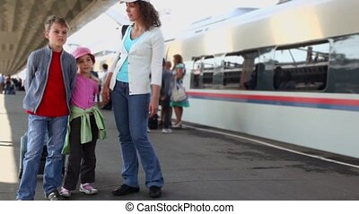 Mother speaks with kids when they stand together at station...