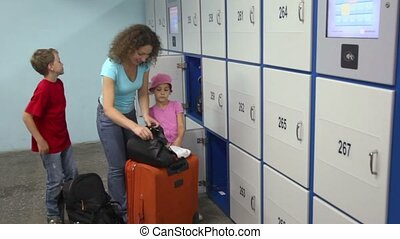 Woman prepares luggage before put it in storage box and her...