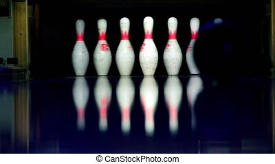 Ball rolls and beats skittles at bowling lane lit in dark,...