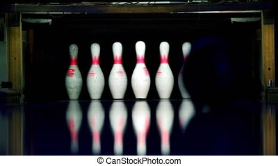 Ball rolls and beats ninepins at bowling lane lit in dark,...