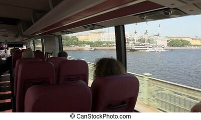 Panorama inside tourists bus ride by bridge over Neva river...
