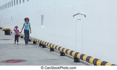 Mother with daughter walk by quay near board of huge liner