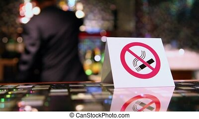 No smoking symbol on plate at table and man moves at...