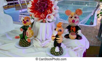 Table adornment with fruit statuettes and ice sculpture near...