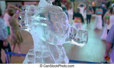 Ice sculpture of horsefish and many people dance at huge hall