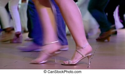Many people dance in latin american style, only legs are visible
