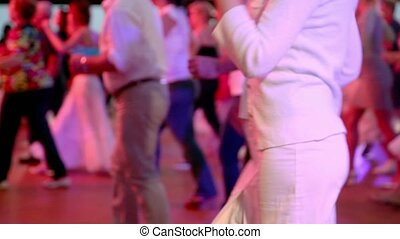 Woman dances with many other people at lage hall - Woman in...