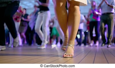 Many people dance in latin american style and clap hands