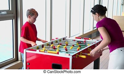 Mother plays table football with her son during cruise