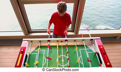 Little boy plays table football and sea are in window behind