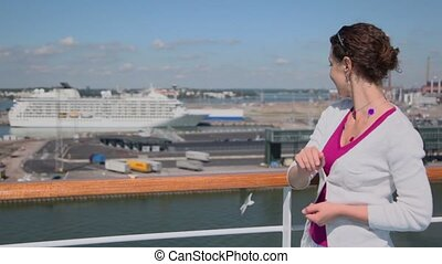 Woman puts piece of bread on handrail and gull takes it, at...