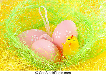 Chick and easter eggs in the yellow nest