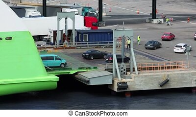 Cars ride from ferry boat in dock with truck parking