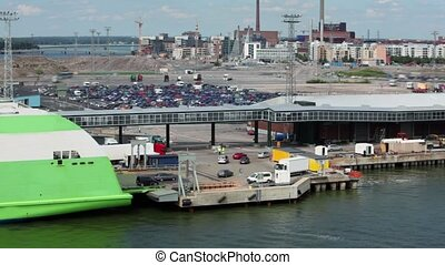 Cars ride from ferry boat in dock with huge parking near...
