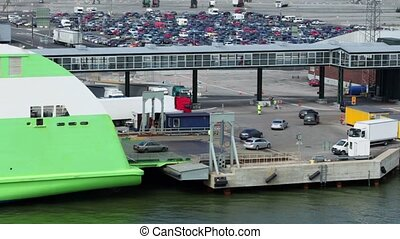 Cars ride from ferry boat in dock with huge parking