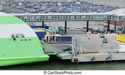 Automobiles ride to ferry boat in dock with huge parking...