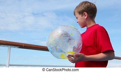 Little boy stand near railing and hold inflated ball with...
