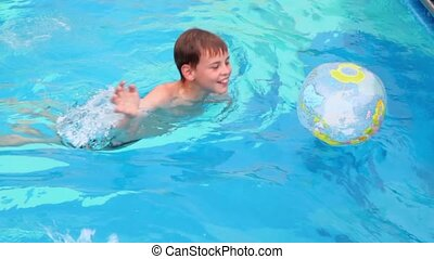 Little boy swims in pool and play with inflated ball