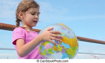 Little girl hold inflated ball and reads aloud near railing