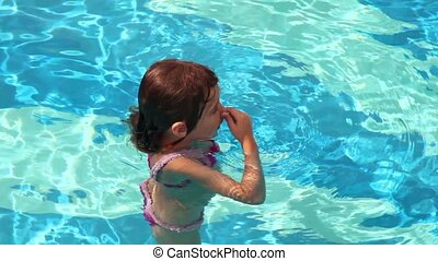 Little girl plunges in pool water and swim with many...