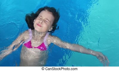 Little girl lies on her back and swims in pool water